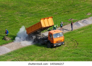 Saint Petersburg,Russia - June 20,2019: Dump truck KAMAZ pours gravel on a pedestrian path in the city square and raised clouds of dust. Working laborers with shovels.