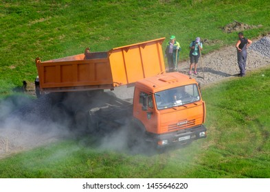 Saint Petersburg,Russia - June 20,2019: KAMAZ truck poured gravel on a pedestrian path in the city square and raised clouds of dust. Are the labourers with shovels.