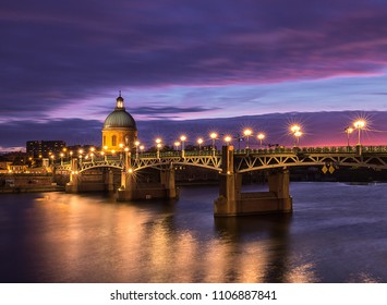 Saint Pierre bridge and Saint Joseph Chapel at sunset. Amazing reflection in the river Garonne. Toulouse, France. Europe. Long exposure photography