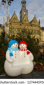 Saint Quentin / France - 12 24 2018: snow man and snow woman, cute bench for couples standing in the main square of the city Saint Quentin, Upper Picardy region, northern France, Europe
