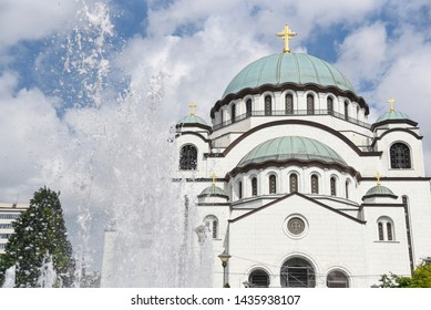 Saint Sava christian catedral with cloudy blue sky and aplshing fountain in front of it in the capital Belgrade