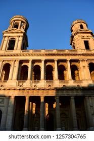 Saint Sulpice Church, Paris, France. Neoclassical facade with sunset light. Blue sky.