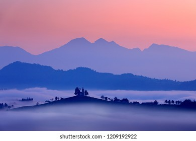 Saint Thomas Church, Sveti Tomaz nad Praprotnim, Skofja Loka. Landscape in Slovenia, nature in Europe.  Foggy Triglav Alps with forest, travel in Slovenia. Beautiful sunrise with sky, green nature.