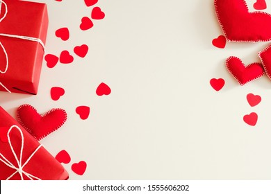 Saint Valentine day. Flat lay arrangement of red handmade felt hearts and gift boxes on white background. Copy space.