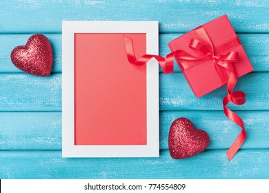 Saint valentine day greeting card. Frame, gift box and red heart on turquoise wooden background top view