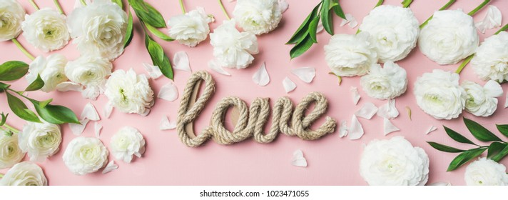 Saint Valentines Day background. Flat-lay of white ranunculus flowers and word love over light pink pastel background, top view. Greeting card or wedding invitation