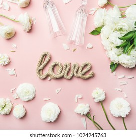 Saint Valentines Day background. Flat-lay of white ranunculus flowers, champaign glasses and word love over light pink background, top view. Greeting card or wedding invitation