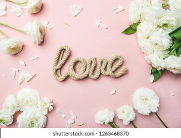 Saint Valentines Day background. Flat-lay of white ranunculus flowers and word love over light pink background, top view. Greeting card or wedding invitation