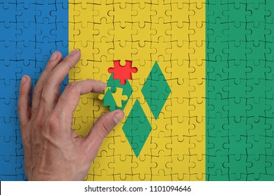 Saint Vincent and the Grenadines flag  is depicted on a puzzle, which the man's hand completes to fold