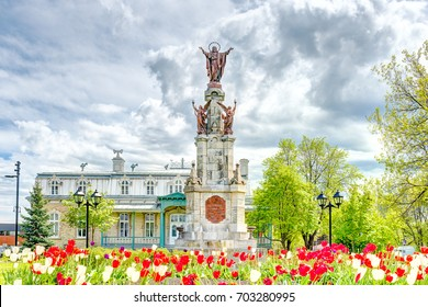 Saint-Augustin-de-Desmaures, Canada - May 29, 2017: Parish of Sainte Augustin in small town on Chemin du Roy with statue of Jesus Christ and tulips