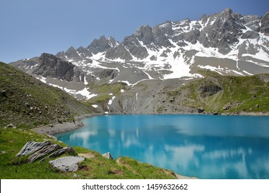 Sainte Anne lake located above Ceillac village after two hours hike, with reflections of mountain range covered with snow, Queyras Regional Natural Park, Southern Alps, France