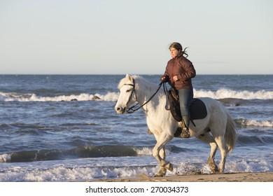 SAINTES-MARIES-DE-LA-MER FRANCE- April 1, 2015: Female Gardian rides her Camargue White Horse on the Mediterranean Sea on April 1, 2015 at Saintes-Maries-de-la-Mer France.
