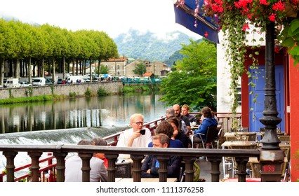 SAINT-GIRONS, FRANCE - AUGUST 19th, 2017 : People relaxing at the open cafe terrasse by the river in the beautiful french mountain village Saint-Girons in Pyrenees.