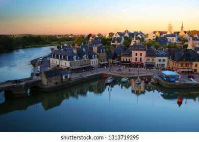 SAINT-GOUSTAN, FRANCE - March 10, 2012: Saint-Goustan harbour city during sunset. Houses, restaurants and people. Reflexion water of boats and houses. Brittany, France.