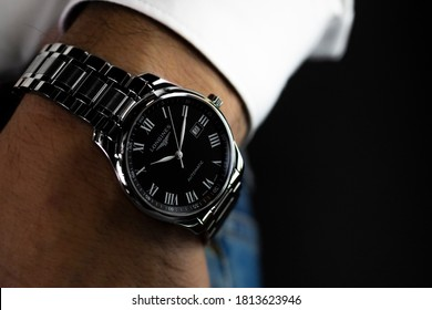 Saint-Imier, Switzerland 31.03.2020 - Closeup fashion image of Longines watch on wrist of man: man's hand in blue jeans pocket with white cuff of plaid shirt. Longines man watch stainless steel case