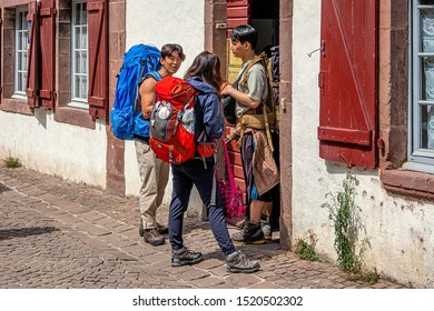 SAINT-JEAN-PIED-DE-PORT, FRANCE - AUGUST 20, 2019. The town is located on 3 paths of Saint-Jacques-de-Compostelle. Three young pilgrims with their backpacks enter a shelter for the night.