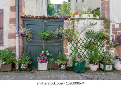 SAINT-JEAN-PIED-DE-PORT, FRANCE - AUGUST 20, 2019. The town is on 3 paths of the pilgrimage of Saint-Jacques-de-Compostelle. Entrance door of a house with many flowers for decoration.
