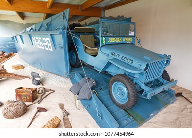 Saint-Laurent-sur-mer, France - August 2, 2014: WWII equipment (USA landing craft (LCVP, Higgins boat) with vehicle) in the museum Musee Memorial d'Omaha Beach, in Normandy, France, on August 2, 2014