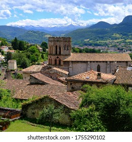 Saint-Lizier, Ariège,France 06/12/20 Terracotta tiled roof of a hill top village. Gothic-style octagonal belfry. Trees and distant Pyrenean mountain range. Snow topped peaks and cumulus clouds