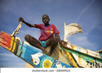 SAINT-LOUIS, SENEGAL, DEC 4: African young kid sitting on a colored fisher boat with UNICEF t-shirt and a blue sky in the background. Saint Louis, Senegal 2010