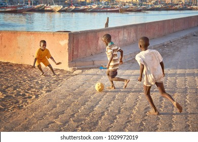 SAINT-LOUIS/SENEGAL - NOVEMBER 13, 2013: African children playing football on the street of Saint-Louis