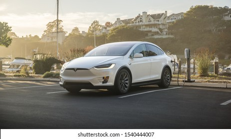 Saint-Malo / France, October 24th 2019 : Photograph of a white Tesla model X charging near a the harbour front.