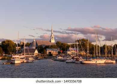 Saint-Michel-de-Bellechasse marina seen during a late afternoon summer golden hour, with sailboats, historical 1873 church and waterside restaurant in the background, Quebec, Canada