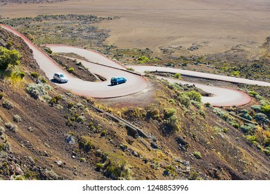 Saint-Paul De La Reunion, France - December 05, 2010: Cars pass by the road across Plaine des Sables at 2260 m above sea level near Piton de la Fournaise volcano in Saint-Paul De La Reunion, France.