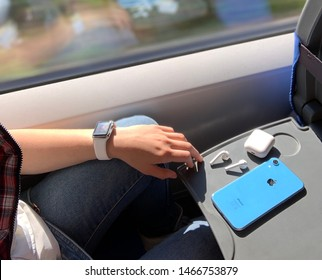 Saint-Petersburg 05.16.2019 Listening to music on your phone on the train, while traveling at the window. Blue iPhone xr, headphones AirPods, Apple Watch.