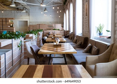 Saint-Petersburg, Creative space Tkachi, May 2017. Wooden white bricks wall loft interior cafe, coffee shop, coworking area. Tables, chairs, plants and retro lights