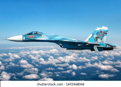 SAINT-PETERSBURG REGION, RUSSIA - July 25, 2019: Sukhoi Su-33 carrier-based jet fighter of Russian Navy during Navy parade rehearsal escorting Tupolev Tu-142MZ
