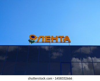 Saint-Petersburg, Russia. 07.07.2019. Hypermarket Lenta sign with sunflower logotype against the blue sky. Lenta is one of the largest retail chains in Russia.