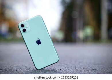 Saint-Petersburg, Russia - 09.09.2020. Shockproof iPhone 11 falling, crashes on asphalt, broken Apple smartphone flying down to ground. Destroyed, damaged phone. Accident with gadget. Crash test.