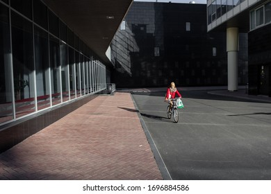 Saint-petersburg, Russia - 4 April 2020: The empty street. Young woman in red jacket with with a bag of groceries rides a bike. People are staying home because of coronavirus COVID-19 outbreak.