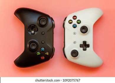 SAINT-PETERSBURG, RUSSIA - APRIL 13, 2018: Black and white joystick xbox one s gamepad, game console on pink background. Computer gaming competition videogame control confrontation concept
