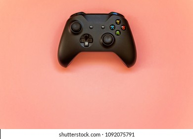 SAINT-PETERSBURG, RUSSIA - APRIL 13, 2018: Black joystick xbox one s gamepad, game console on pink pastel background. Computer gaming competition videogame control concept