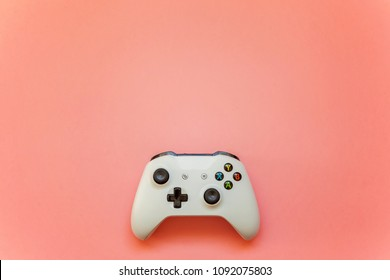 SAINT-PETERSBURG, RUSSIA - APRIL 13, 2018: White joystick xbox one s gamepad, game console on pink pastel background. Computer gaming competition videogame control concept