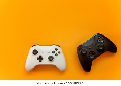 SAINT-PETERSBURG, RUSSIA - APRIL 13, 2018: Black and white joystick xbox one s gamepad, game console on yellow background. Computer gaming competition videogame control confrontation concept