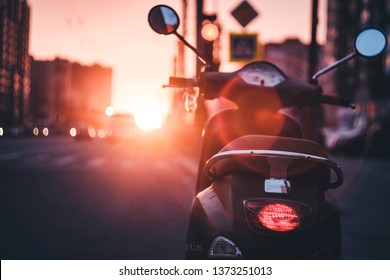 SAINT-PETERSBURG, RUSSIA - APRIL 17, 2019: piaggio vespa scooter parking on the street on the sunset background. Toned and dramatic.