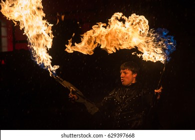 "SAINT-PETERSBURG, RUSSIA - APRIL 22, 2017 : A firedancer blows fire with two small flamethrowers  on ""Festival of Light"" under heavy rain"