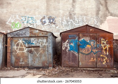 Saint-Petersburg, Russia - April 3, 2015: Old rusted locked garages with grungy graffiti. Vasilievsky island, Central old part of St. Petersburg city
