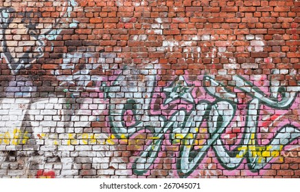Saint-Petersburg, Russia - April 3, 2015: Urban brick wall with grungy chaotic graffiti. Vasilievsky island, Central old part of St. Petersburg city