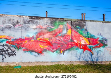 Saint-Petersburg, Russia - April 6, 2015: Colorful graffiti with chaotic red pattern over old gray concrete garage walls