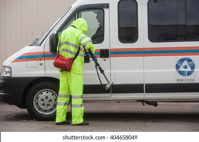 Saint-Petersburg, Russia - April 6, 2016: A man in a special protective suit green measures the level of radiation on the car after a decontamination treatment.