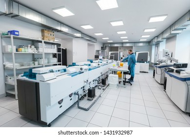Saint-Petersburg, Russia - April 6, 2018:  Hospital laboratory, technical specialist in blue medical gown works with clinical lab equipment