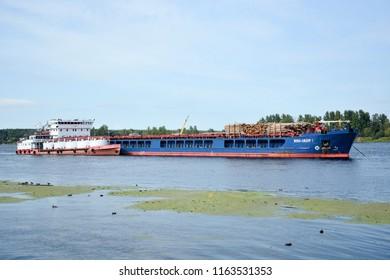 SAINT-PETERSBURG, RUSSIA- AUGUST, 21, 2018: Big shipwith wooden cargo on Neva river