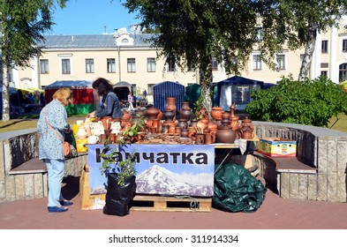 "SAINT-PETERSBURG, RUSSIA - AUGUST 30, 2015 - Agricultural Fair ""Agrorus"" in St. Petersburg. A woman chooses clay dishes"