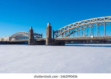 Saint-Petersburg. Russia. Bolsheokhtinsky bridge over frozen Neva river. Peter the Great bridge. Winter Petersburg. Neva river. Petersburg bridges. Russian cities. Petersburg road architecture.