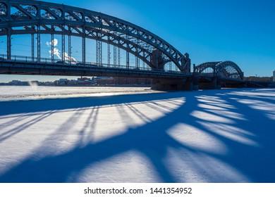 Saint-Petersburg. Russia. Bridge over frozen water. Peter the Great bridge. Bolsheokhtinsky bridge. Frozen Neva river. Petersburg bridges. Russian cities. Petersburg road architecture.