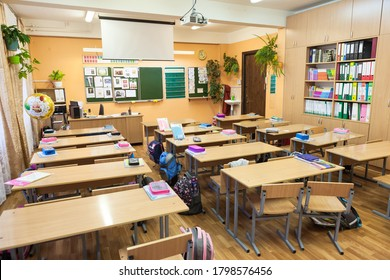 Saint-Petersburg, Russia, circa Sep, 2017: Russian schoolclass with many pupil desks, teacher table and green blackboard. School bags and textbooks are on tables at breaktime